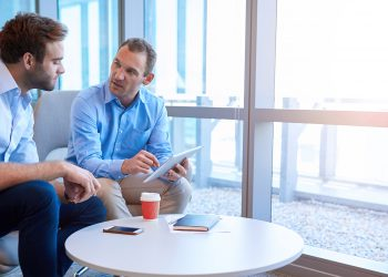 Handsome middle-aged business executive sitting with a younger coworker in a bright modern office, explaining some information to him on a digital tablet; Shutterstock ID 433567450; PO: .; Job: .; Client: Generali; Other: .